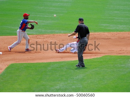 LAKE BUENA VISTA, FL - Phillies shortstop Jimmy Rollins throws the ball as the pivot of a double play with a Brave baserunner sliding in during the March 24, 2010 game in Lake Buena VIsta, FL - stock photo