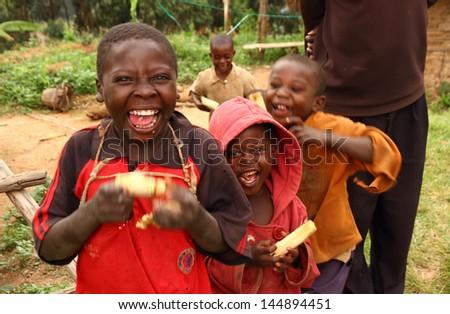 LAKE BUNYONI, UGANDA - CIRCA SEPTEMBER 2012.  A group of unidentified Ugandan children smile while enjoying eating sugarcane near Lake Bunyoni, Uganda during September 2012. - stock photo