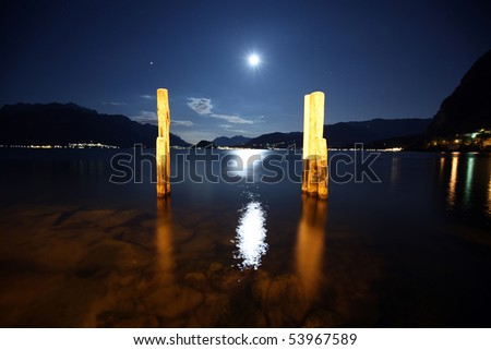 Lake Como, Italy, night, water, moon path, the reflection of the cloudless sky, stars, a pier for the ferry, - stock photo