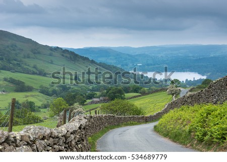 Lake District, England - May 30, 2012: Rural road with stone walls on the side meanders through the landscape. Shot from above shows lake downhill. Green meadows, forests and ferns. Hazy horizon.