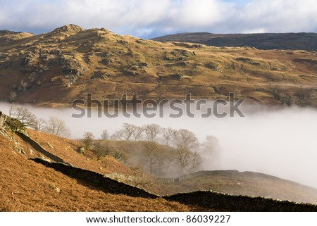 lake district landscape view sunny peaks as morning mist moves up the valley - stock photo