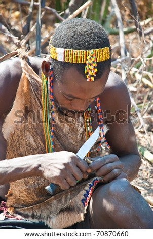LAKE EYASI, TANZANIA - AUGUST 14: an unidentified man from Hadza tribe, build an arrow, on august 14, 2010. Hadza people are an ethnic group in north Tanzania, who live hunting wild animals - stock photo