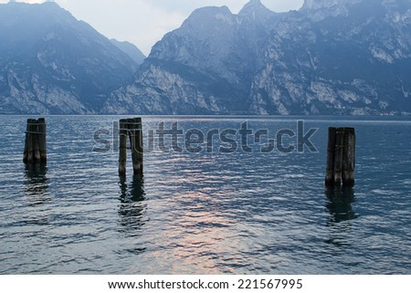 Lake Garda at sunset in the evening mist and twilight - stock photo