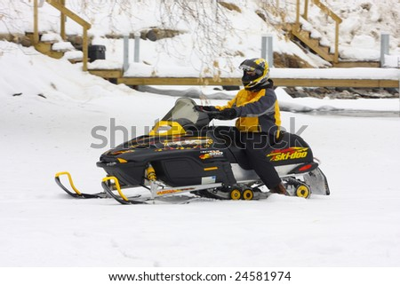 LAKE GEORGE, NY - February 7, 2009: A snowmobile rider exits the ice on Lake George in order to enjoy the  February 7 , 2009 Lake George Winter Carnival.