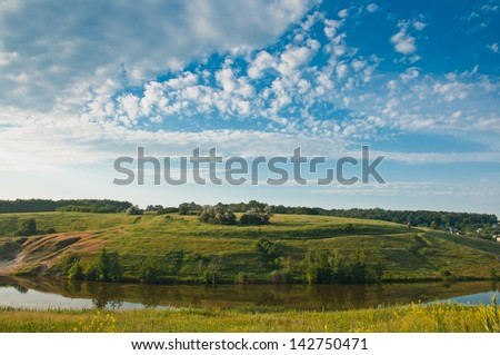 lake, green grass and white clouds on blue sky
