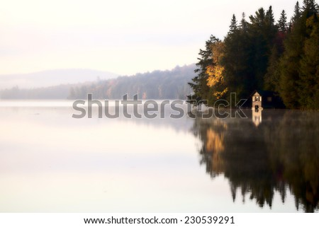 Lake in Autumn Algonquin Muskoka Ontario colors boat house - stock photo