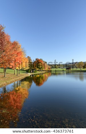 Lake in Autumn Surrounded by Trees in Fall Colors - stock photo