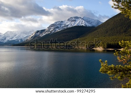 Lake in Rockies with mountains on background - stock photo