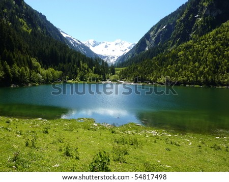 Lake in the Alps with a glacier in the background - stock photo