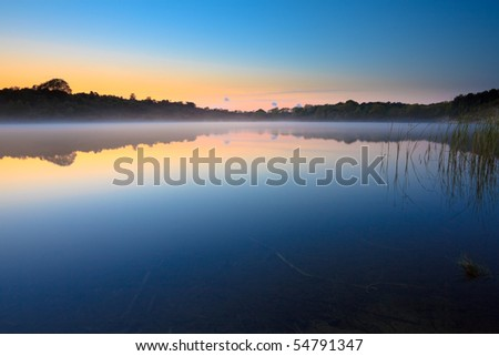 Lake in the mist at sunset - stock photo