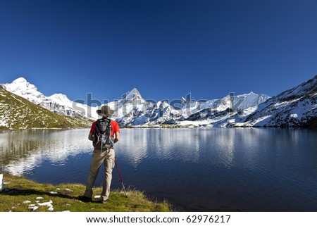Lake in the mountains with reflexion and hiker
