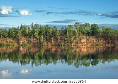 Lake in wood open-cast mine - stock photo