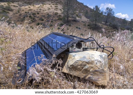 LAKE ISABELLA, USA - MAY 24, 2016: When hiking or living off the grid a folding solar charger is a convenient way to keep small cameras and other devices powered up. - stock photo