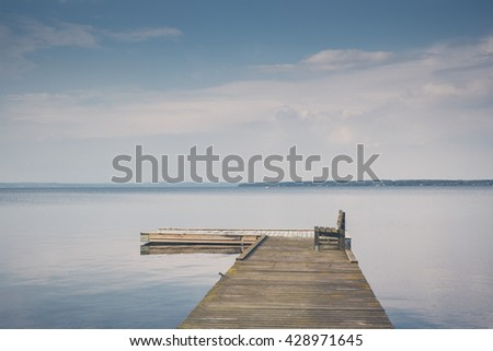 Lake jetty peer with wooden bench with beautiful sky clouds on sunset travel vacation. Print on canvas