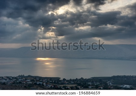 Lake Kinneret in the morning, sun rays are shining through the clouds  - stock photo
