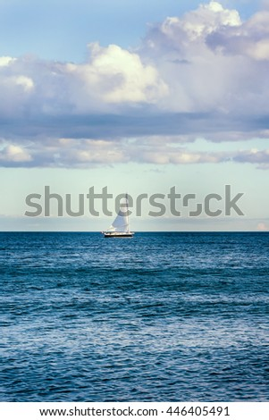 Lake landscape with a sail boat in the distance - stock photo