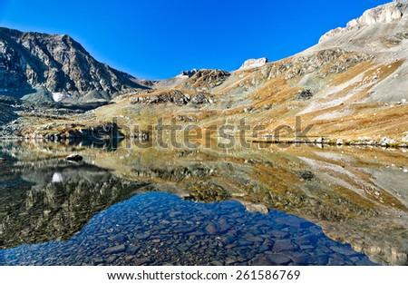 Lake like the mirror, symmetric view. Picture was taken during trekking hike in the magnificent and stunning Caucasus mountains at autumn, Arhiz region, Abishira-Ahuba range,Karachay-Cherkessia,Russia - stock photo