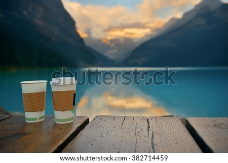 Lake Louise with coffee cup at sunrise in Banff national park with mountains and forest in Canada. - stock photo