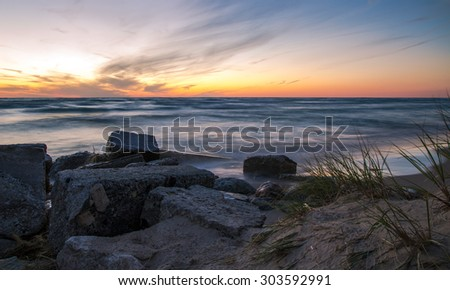 Lake Michigan Sunset. The sunset along the coast of Lake Michigan in Ludington State Park. Ludington is often voted as Michigan's top state park and one of the most popular in America. - stock photo