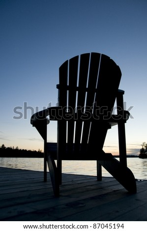 Lake Of The Woods, Ontario, Canada; Empty Deck Chair On A Pier Next To A Lake - stock photo
