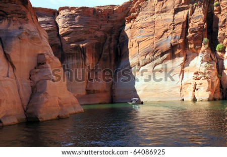 Lake Powell, in Glen Canyon spans 186 miles  in Utah and Arizona.  its coastline is populated with colorful sandstone cliffs,  pristine blue green water, islands, rock formations, resorts and marinas - stock photo