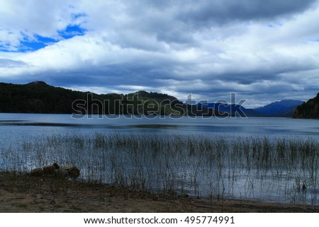 lake, reed and beach with dark clouds in the mountains