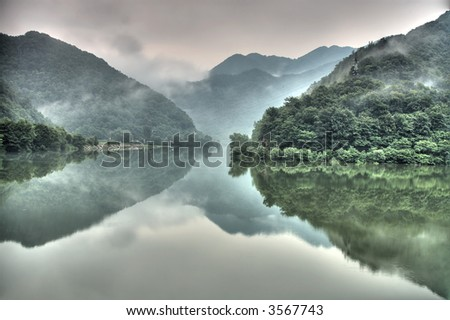 Lake reflection of a green forest - stock photo