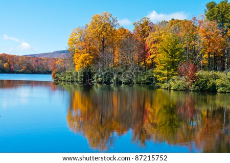 Lake reflections of fall foliage. Colorful autumn foliage casts its reflection on the calm waters of a North Carolina lake along the Blue Ridge Parkway. - stock photo