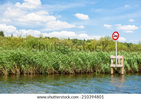 Lake scenery with a red no boating sign - stock photo