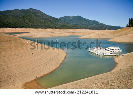 Lake Shasta, CA, August 20, 2014 -- California's lingering drought exposes the 180-200 foot drop in water levels. The state's largest reservoir is receding at an average of 4.9 inches per day.  - stock photo