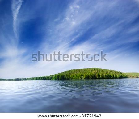 Lake shore under blue sky - stock photo
