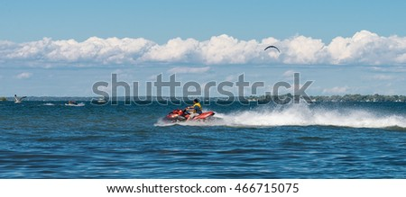 Lake Simcoe, Ontario - August 6, 2016: An unidentified man is racing on his red jet ski across blue waters of Lake Simcoe