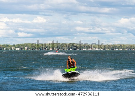 Lake Simcoe, Ontario - August 21, 2016: Jet ski drivers are racing across Lake Simcoe against the backdrop of the shoreline with cottages and a ferry