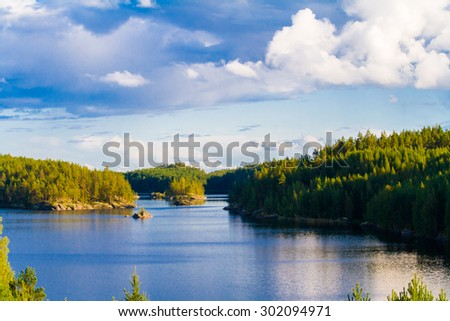 Lake summer view with reflection of clouds on water surface, Finland - stock photo