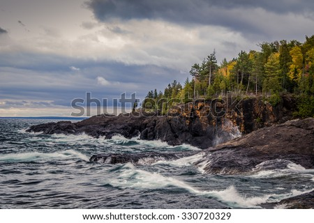 Lake Superior Coast, Gray sky and stormy seas crash on the cliffs of the black rocks along the shores of the Lake Superior coast. Presque Isle Park. Marquette, Michigan. - stock photo