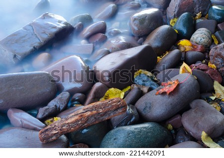 Lake Superior light waves on shore with colorful fall leaves - stock photo