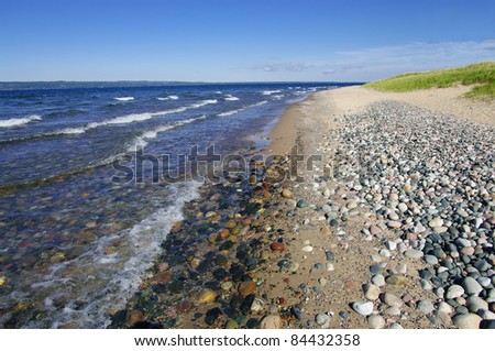 Lake Superior Shoreline:  Light waves wash a shore of sand and rounded rocks at Whitefish Bay on Michigan's Upper Peninsula. - stock photo