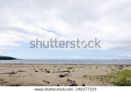 Lake Superior Shoreline. Waves come to a shore of sand - stock photo