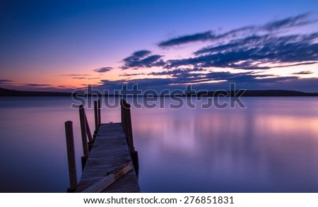 Lake Superior Sunrise. Sunrise over the Lake Superior horizon with a dock in the foreground and Grand Island in the background. - stock photo