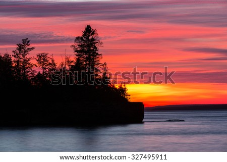 Lake Superior Sunset - A fiery blaze lights the sky from this late day sunset and creates a silhouette of the jack pines on this peninsula. Five Mile Point in the Upper Peninsula of Michigan. - stock photo