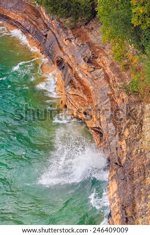 Lake Superior waves crash into the cliff base at Miner's Castle in Upper Peninsula Michigan's Pictured Rocks National Lakeshore. - stock photo