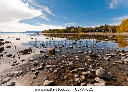 Lake Tahoe in fall with reflections of trees and the sky - stock photo