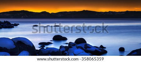 Lake Tahoe Nevada Sunset with rocks and smooth water - stock photo