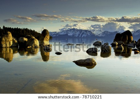 Lake Tahoe,  Zephyr Cove with calm blue water large rocks in the water with Mountains in the background - stock photo