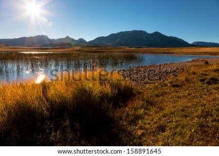 Lake towards the sun with mountains in background - stock photo