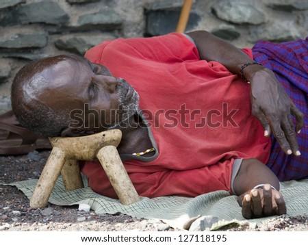 """LAKE TURKANA, KENYA - JANUARY 12:  El molo man resting on traditional """"head rest"""". January 2013 at Lake Turkana - stock photo"""