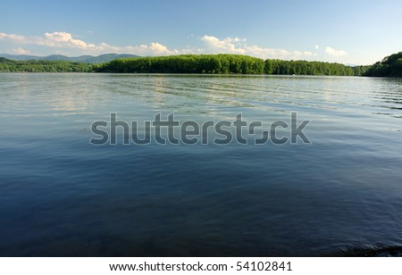 Lake under mountains - stock photo