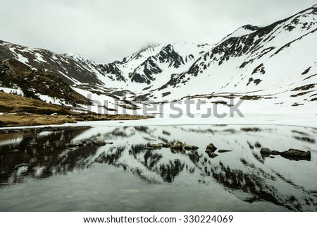 Lake under the Pic Carlit, covered by snow, Pyrenees (France) - stock photo