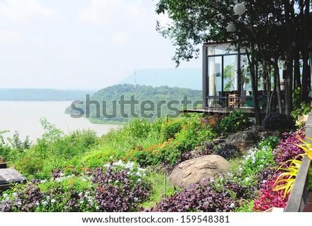 Lake view veranda and beautiful flower garden on the cliff - stock photo
