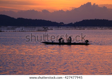 Lake view with fisherman on colorful boat in morning time.  - stock photo